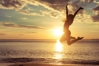 44757448 - happy teen girl jumping on the beach at the sunset time